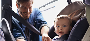 father buckling infant into car seat