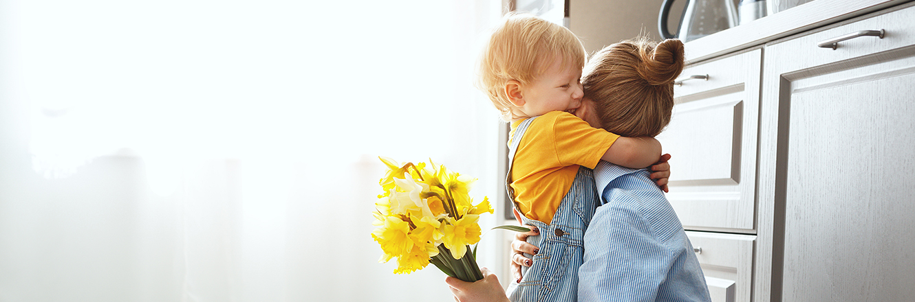 mother hugging child in kitchen and holding flowers