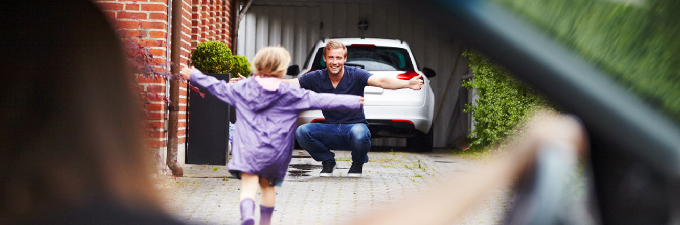A young daughter running to her father in front of their garage