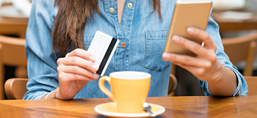 woman using phone and card in cafe with tea cup
