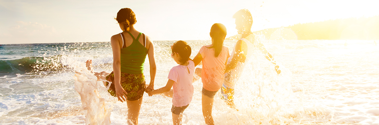 family holding hands in water at beach