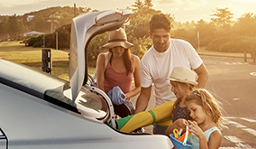 family getting beach toys out of trunk