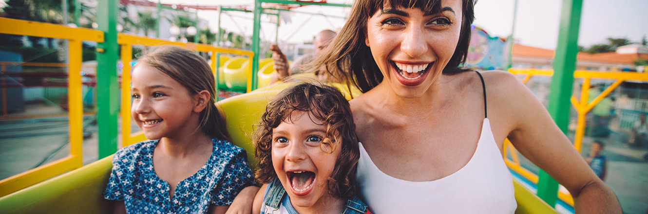 Happy mom and two kids riding a fun roller coaster