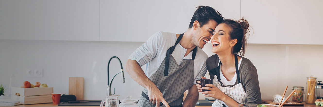 young couple laughing while cooking together in kitchen