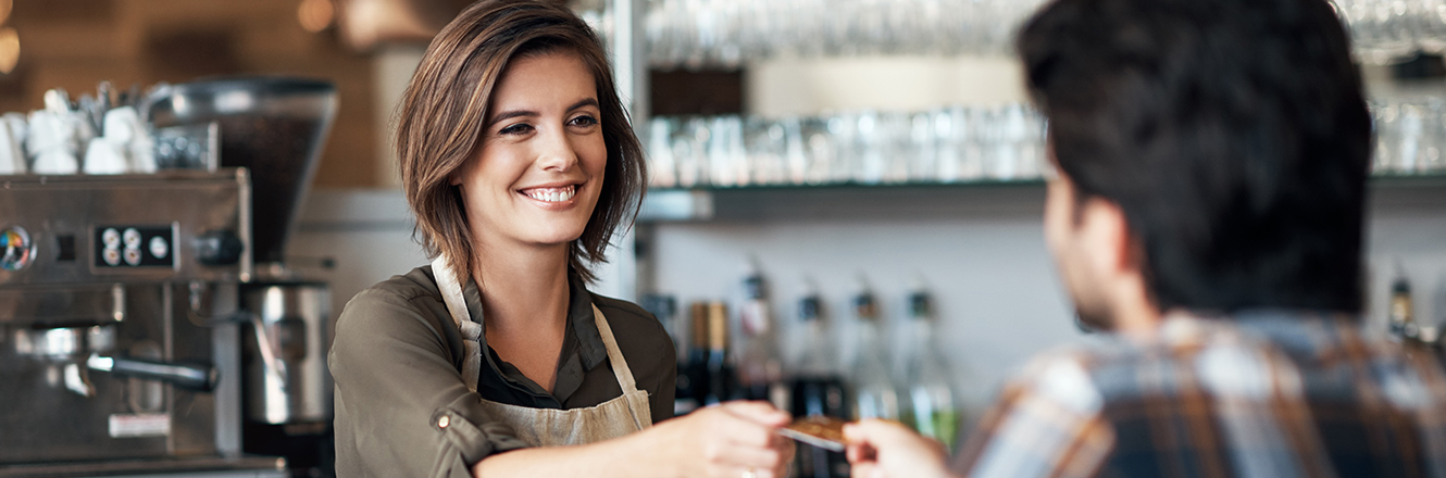man handing debit or credit card to barista at coffee shop
