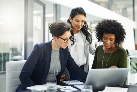 Three women review work together on computer in a bright office building