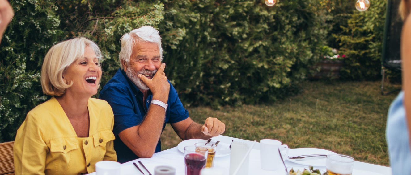 A mature couple laughing at an outdoor dinner