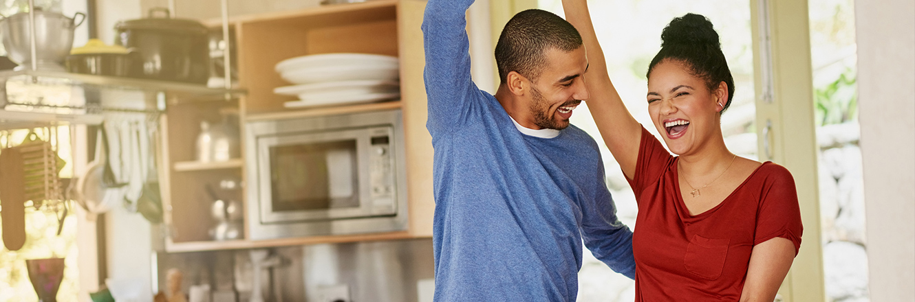 couple dancing in home kitchen