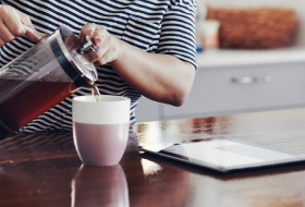 A woman pouring coffee in a kitchen