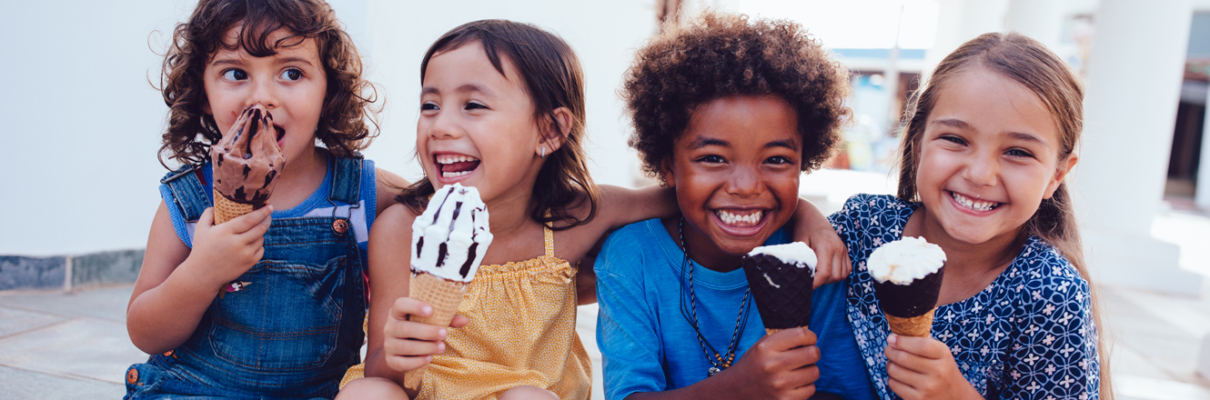 group of kids laughing and eating ice cream in summertime