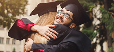 two high school graduates hugging after graduation