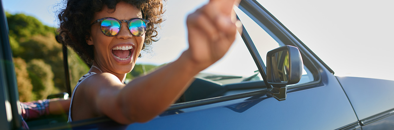 Woman in sunglasses smiling and putting up a peace sign in the passenger seat of a convertible car