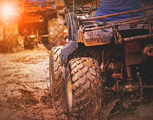 Two ATV's driving through a muddy trail