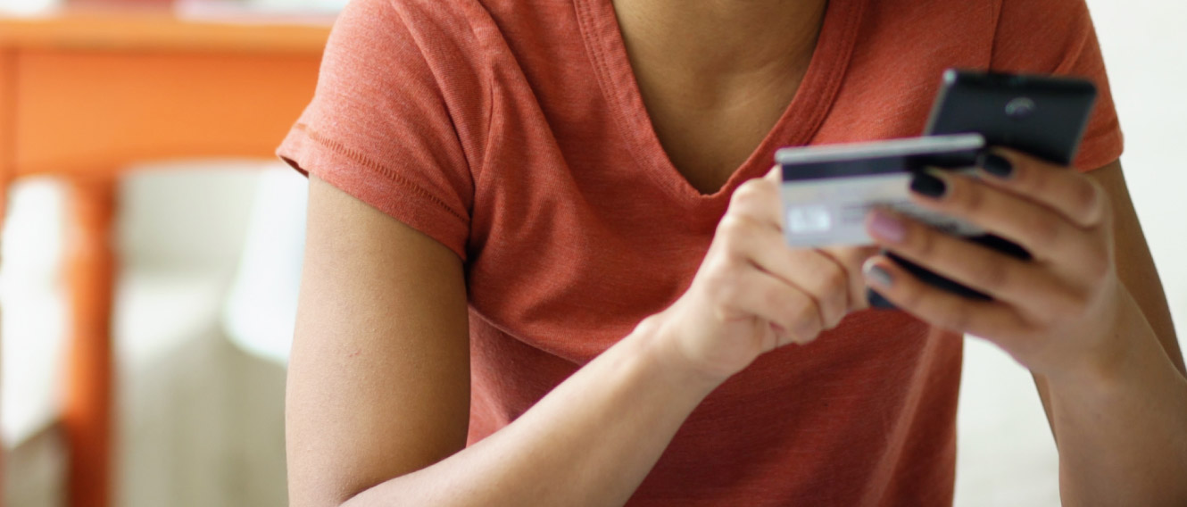 A woman using a debit/credit card while on a mobile device