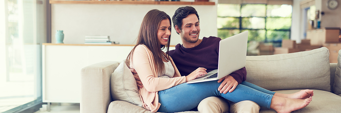 couple sitting on couch with laptop