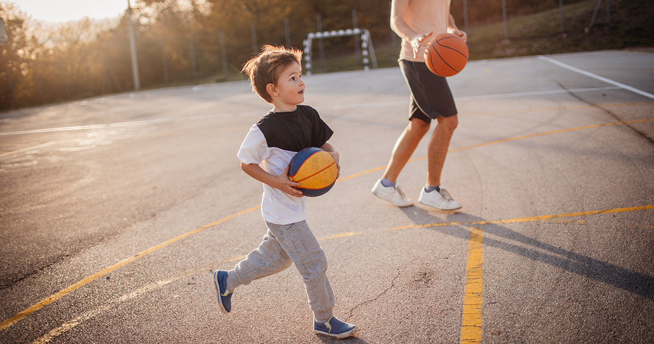 young boy playing basketball with dad