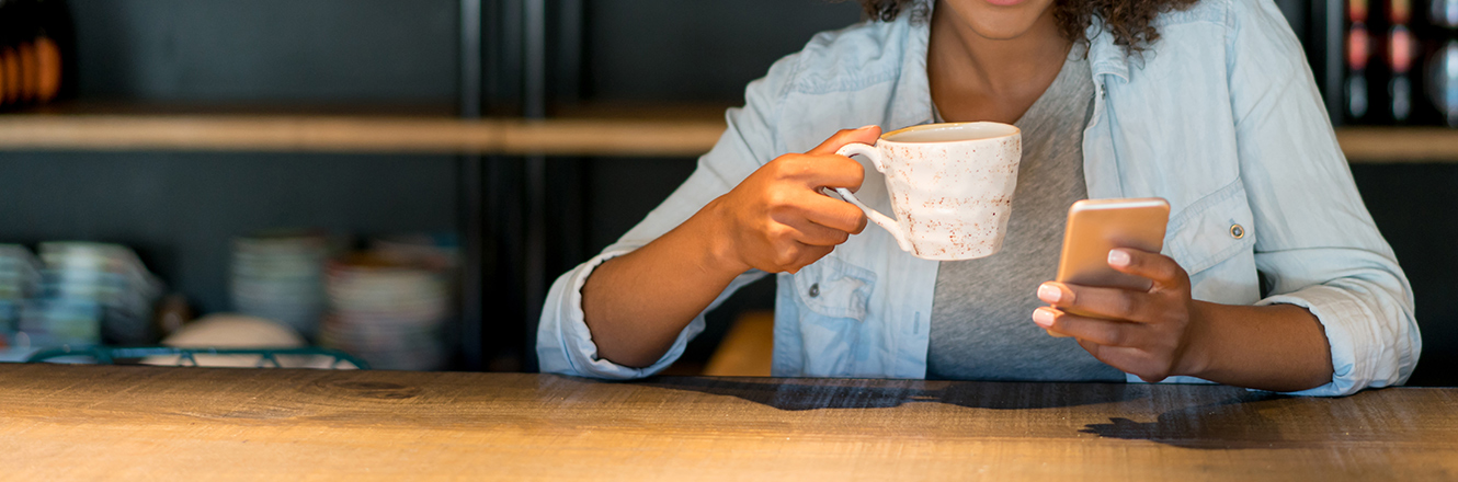 woman looking at phone holding coffee cup at table