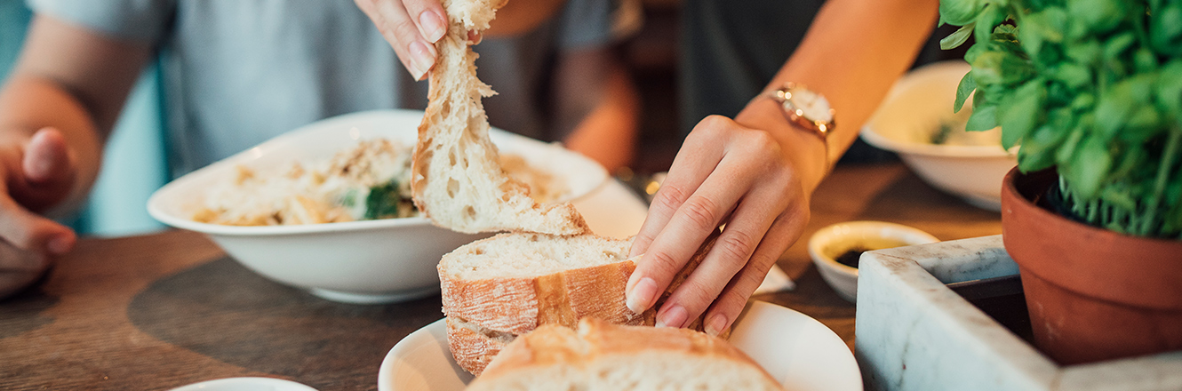 Woman tearing piece of bread at restaurant
