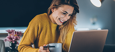 young woman using laptop with coffee cup and credit card