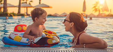 mother and toddler son in pool at resort