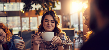 woman sitting in coffee shop holding mug