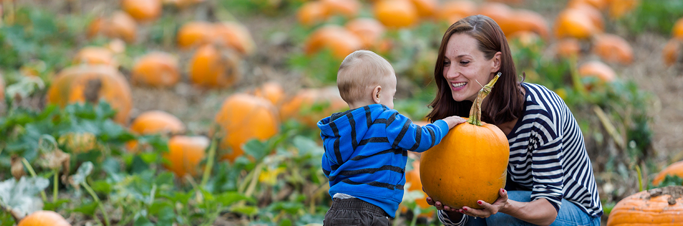 mother and toddler son at pumpkin patch