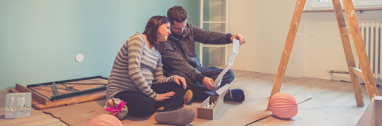 couple sitting on floor looking at renovation plans
