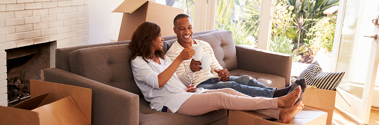 couple sitting on couch with coffee, surrounded by moving boxes