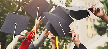graduates holding caps in the air