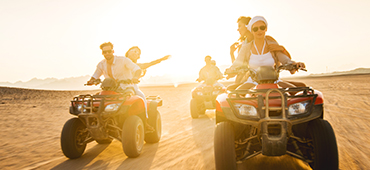couples driving ATVs through desert