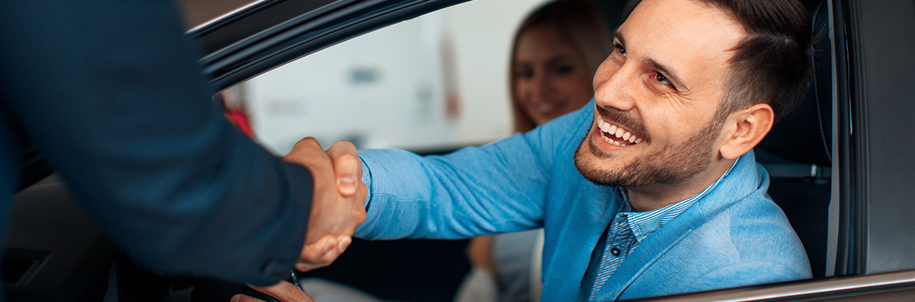 Man leaning out car window to shake hands with salesperson